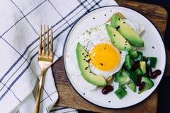 Zdrowy śniadanie grzanka z avocado, całej banatki chleb, smażąca burrito sałatka na bielu talerzu i jajko, i obraz royalty free