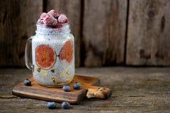 Zdrowy śniadanie jest puddingiem z chia ziarnami, agawa syropem, mlekiem, figami i zamarzniętymi jagodami, malinki i czarne jagod Fotografia Stock