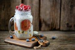 Zdrowy śniadanie jest puddingiem z chia ziarnami, agawa syropem, mlekiem, figami i zamarzniętymi jagodami, malinki i czarne jagod Obrazy Royalty Free