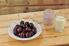 Zdrowy śniadanie komponuje talerz wiśnia, szkło mleko i słój jogurt na płótnie z drewnianym tłem, Fotografia Royalty Free