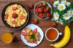 Zdrowy śniadanie: kukurydzani płatki, truskawki, sok, herbata i cro, Obrazy Royalty Free