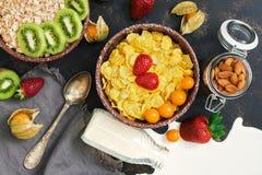 Zdrowy śniadanie na ciemnym tle, rozlewający mleko, kałuża Muesli, cornflakes, truskawki, kiwi, dokrętki najlepszy widok zdjęcia royalty free