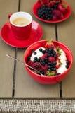 Zdrowy śniadanie na ogrodowym meble: chałupa ser z kwaśną śmietanką, truskawką, malinką i czarną jagodą, kawa espresso Fotografia Royalty Free