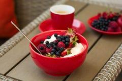 Zdrowy śniadanie na ogrodowym meble: chałupa ser z kwaśną śmietanką, truskawką, malinką i czarną jagodą, kawa espresso Obraz Royalty Free