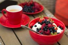 Zdrowy śniadanie na ogrodowym meble: chałupa ser z kwaśną śmietanką, truskawką, malinką i czarną jagodą, kawa espresso Obraz Stock