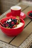 Zdrowy śniadanie na ogrodowym meble: chałupa ser z kwaśną śmietanką, truskawką, malinką i czarną jagodą, kawa espresso Zdjęcia Royalty Free