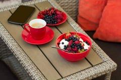 Zdrowy śniadanie na ogrodowym meble: chałupa ser z kwaśną śmietanką, truskawką, malinką i czarną jagodą, kawa espresso Fotografia Stock