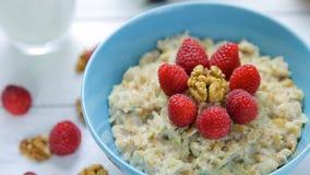 Zdrowy śniadanie - oatmeal z malinkami i orzechami włoskimi w puchar pozyci na drewnianym stole świeżymi, dojrzałymi, z bliska zbiory wideo
