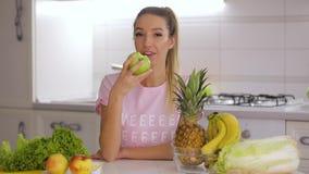 Zdrowy śniadanie, szczęśliwej uśmiechniętej kobiety łasowania zieleni świeży jabłko na kuchni zdjęcie wideo