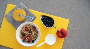 Zdrowy śniadanie z granola, greckim jogurtem, jabłkiem, jagodami i świeżym sokiem pomarańczowym na żółtej tnącej desce na szarym  obraz stock