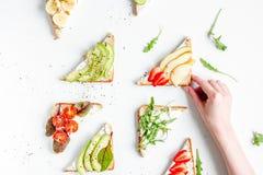 Zdrowy śniadanie z kanapkami ustawia i ręki na białego tła odgórnym widoku Fotografia Royalty Free