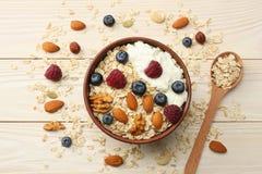 zdrowy śniadaniowy oatmeal, czarne jagody, malinki i dokrętki na białym drewnianym stole, Odgórny widok zdjęcie stock