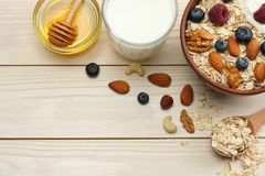 Zdrowy śniadaniowy oatmeal, czarne jagody, malinki, mleko, miód i dokrętki na białym drewnianym stole, Odgórny widok z kopii prze zdjęcia royalty free