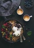Zdrowy śniadaniowy owsa granola rozdrobni z świeżymi jagodami, ziarnami i lody w żelaznej rynienki niecce na ciemnej drewnianej d Obrazy Royalty Free