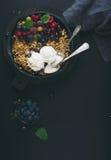 Zdrowy śniadaniowy owsa granola rozdrobni z świeżymi jagodami, ziarnami i lody w żelaznej rynienki niecce na ciemnej drewnianej d Obraz Stock