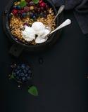 Zdrowy śniadaniowy owsa granola rozdrobni z świeżymi jagodami, ziarnami, lody i nowymi liśćmi w żelaznej rynienki niecce na zmrok Obrazy Royalty Free