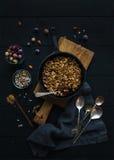 Zdrowy śniadaniowy owsa granola rozdrobni z zamarzniętymi świeżymi jagodami i ziarnami w irom rynienki niecce na nieociosanej dre Zdjęcie Royalty Free