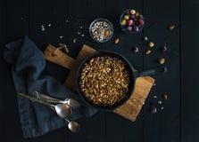 Zdrowy śniadaniowy owsa granola rozdrobni z zamarzniętymi świeżymi jagodami i ziarnami w irom rynienki niecce na nieociosanej dre Obraz Royalty Free