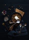 Zdrowy śniadaniowy owsa granola rozdrobni z zamarzniętymi świeżymi jagodami, ziarnami i lody scoopin irom rynienki niecką, dalej Obrazy Royalty Free