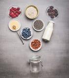 Zdrowy śniadaniowy szklany słój robi z składnikami: chia ziarna, goji jagody, oatmeal, świeże jagody, miód, mleko i jogurt, fotografia royalty free