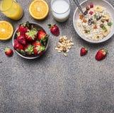 Zdrowy śniadaniowy zboże z wysuszonymi owoc, świeży sok pomarańczowy, talerz truskawki na drewnianym nieociosanym tło odgórnego w Zdjęcia Royalty Free