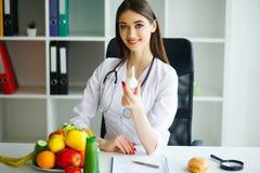 zdrowy Doktorscy dietetyczka chwyty w rękach czosnek zdrowego żywienia Świezi warzywa i owoc na stole zdjęcie royalty free