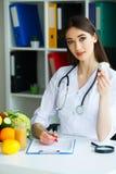 zdrowy Doktorscy dietetyczka chwyty w rękach czosnek zdrowego żywienia Świezi warzywa i owoc na stole obrazy stock