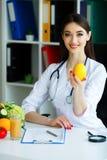zdrowy Doktorska dietetyczka Uśmiecha się cytrynę i Pokazuje Kobieta Trzyma owoc w rękach Potomstwa Fabrykują z Pięknym uśmiechem obraz stock