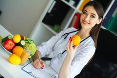 zdrowy Doktorska dietetyczka Uśmiecha się pomarańcze i Pokazuje Kobieta Trzyma owoc w rękach Potomstwa Fabrykują z Pięknym uśmiec zdjęcie stock