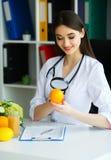 zdrowy Doktorska dietetyczka Uśmiecha się pomarańcze i Pokazuje Kobieta Trzyma owoc w rękach Potomstwa Fabrykują z Pięknym uśmiec zdjęcia stock