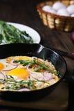 Zdrowy domowej roboty tani jedzenie, jajka i bekon w niecce, fotografia stock