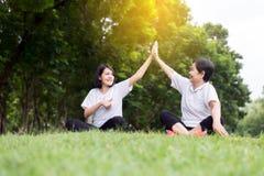 Zdrowy i styl życia pojęcie, Azjatycka kobieta podnosi w górę ręk i relaksuje przy jawnym parkiem w ranku, szczęściu i ono uśmiec fotografia stock