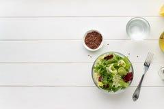 Zdrowy jarski jedzenie: świeża mieszanki sałatka z oleju i lna ziarnem na białym drewnianym tle Fotografia Royalty Free