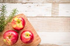 Zdrowy jedzenie: czerwoni jabłka i rozmaryny na drewnianym stole Zdjęcie Stock