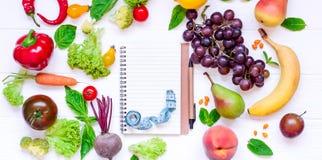 Zdrowy jedzenie, diety łasowanie, detox tło - różni owoc i warzywo, opróżnia otwartego notatnika, i pomiarowa taśma na bielu zale Obrazy Royalty Free