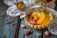 Zdrowy jedzenie jest świeżymi owoc i jagodami, brzoskwinie, jabłka, cranberries, przylądków agresty w koszu od ciasta Zdjęcia Royalty Free