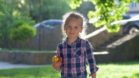 Zdrowy jedzenie, portret szczęśliwa mała blondynki dziewczyna żuć soczystego jabłka w świetle słonecznym plenerowym ubierał szkoc zbiory