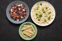 Zdrowy jedzenie w pucharach na dryluje stół Jarzynowa sałatka z quinoa krokietowym, penne makaronem z brokułami i słodką kukurudz obraz stock