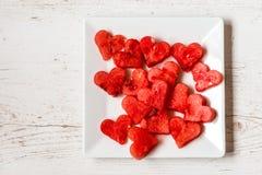Zdrowy jedzenie z miłością Kawałki arbuz w postaci serc na białym drewnianym tle Odgórny widok obraz royalty free