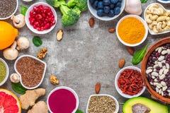 Zdrowy karmowy czysty ?asowanie wyb?r: owoc, warzywo, ziarna, superfood, dokr?tki, jagody na betonowym tle Odg?rny widok obraz stock