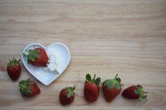 Zdrowy karmowy fotografia wizerunek z świeżymi soczystymi truskawkami w miłość kształta kierowym naczyniu na drewnie z creme frai Obraz Stock