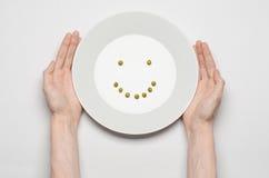 Zdrowy karmowy temat: ręki trzyma talerza zieleni grochy na białym stołowym odgórnym widoku Zdjęcie Stock