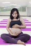 Zdrowy kobieta w ciąży siedzi przy gym Zdjęcia Stock