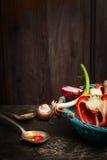 Zdrowy kucharstwo z świeżymi organicznie warzywami i olejem Scena na nieociosanym kuchennym stole nad drewnianym tłem Zdjęcia Stock