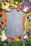 Zdrowy lub jarski karmowy tło z asortymentem świezi rolni warzywa na szarym nieociosanym tle, odgórny widok fotografia stock