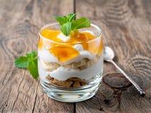 Zdrowy płatowaty deser z jogurtem, banan, mango, ciastko na drewnianym tle, boczny widok fotografia royalty free