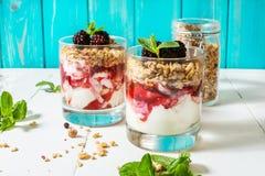 Zdrowy płatowaty deser z jogurtem, granola, dżem, czernica w szkle na drewnianym tle obrazy royalty free