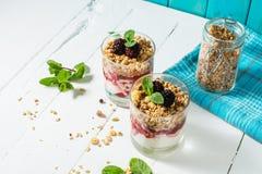 Zdrowy płatowaty deser z jogurtem, granola, dżem, czernica w szkle na drewnianym tle fotografia royalty free