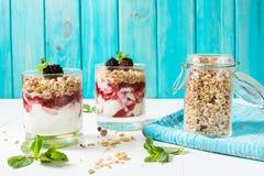 Zdrowy płatowaty deser z jogurtem, granola, dżem, czernica w szkle na drewnianym tle obraz stock