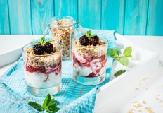 Zdrowy płatowaty deser z jogurtem, granola, dżem, czernica w szkle na drewnianym tle fotografia stock